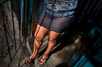 A Salvadoran sex worker stands in the door of a room where her sexual services are offered to clients in San Salvador, El Salvador, 19 December 2013. Although prostitution is not legal in El Salvador, dozens of street sex workers, wearing provocative miniskirts, hang out in the dirty streets close to the capital's historic center. Sex workers of all ages are seen on the streets but a significant part of them are single mothers abandoned by their male partners. Due to the absence of state social programs, they often seek solutions to their economic problems in sex work. The environment of street sex business is strongly competitive and dangerous, closely tied to the criminal networks (street gangs) that demand extortion payments. Therefore, sex workers employ any tool at their disposal to struggle hard, either with their fellow workers, with violent clients or with gang members who operate in the harsh world of street prostitution.