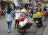 Old lady carrying heavy load in  Hanoi's Old Town  , January 2016.