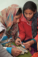 Dehradun, India.  Two Muslim Indian Women Working together in Sewing Instruction Class.