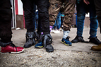 """Velika Kladuša, Bosnia & Herzegovina, 20/12/18. Early morning at Miral camp where people come back from """"the game"""" of the night before. The situation is appalling but apparently """"quite standard"""" for the routine of """"the game"""": broken hands & fingers, injuries & wounds, people's shoes covered with plastic rubbish bags, feet close to the freezing point. Inside the MSF (Mèdecins Sans Frontièrs) mobile clinic - which treats & makes medical referrals for 60+ patients every morning at the camp - a Palestinian guy shows where he was beaten by the 'usual' truncheon: straight to the ribs. The only 'crime' of all these people is to be found trying to cross the border between Bosnia & Croatia: EU external border. In the afternoon, a brave English Professor from the University of Gaza City in Palestine took me to the border crossing point where, during the night (difficult to be documented), illegal """"push-backs"""" are allegedly made by the Croatian border police (1.). In the photos of this part of the story, viewers can spot plain-white vans in front of an unfinished building. These vans allegedly collect people near the border. Then, people are pushed-back down the hill into a river which obviously put them in grave danger of hypothermia and death. This is the reason of the presence of clothes, shoes, duvets left behind in the whole area.<br /> Push-back (respingimenti): «set of state measures by which refugees and migrants are forced back over a border -generally immediately after they crossed it- without consideration of their individual circumstances and without any possibility to apply for asylum or to put forward arguments against the measures taken. Push-backs violate -among other laws- the prohibition of collective expulsions [Article 4 Protocol 4 ECHR; non-humane or degrading treatment or punishment: Article 3 ECHR] stipulated in the EUROPEAN CONVENTION ON HUMAN RIGHTS» (2.).<br /> 1.Video & Article (TheGuardian.com) http://bit.do/fguDj<br /> 2.(Ecchr.eu) http://bit.do/fg"""