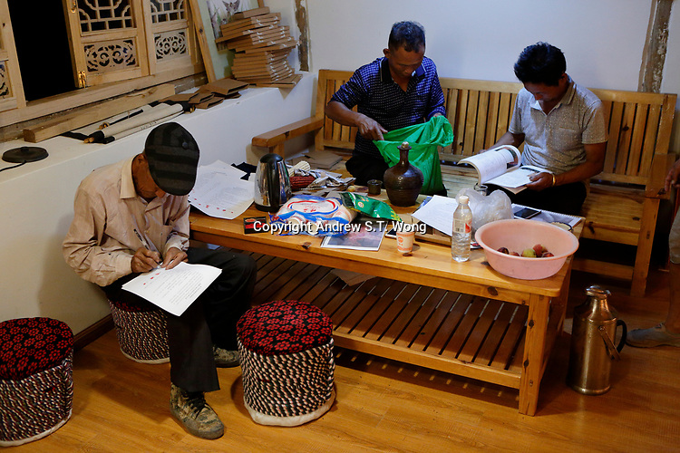 Wumu Village, Yulong County, Yunnan Province, China - Villagers sign documents prepared by Dongba priest He Jixian of the Naxi ethnic group during the inaugural meeting of their agricultural cooperative, June 2019