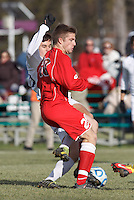 Amherst forward Greg Singer (25) scoring effort thwarted by St. Lawrence defender Austin Roney (20). NCAA Division III Sectionals. In double-overtime, Amherst College (white) defeated St. Lawrence University (red), 2-1, on Hitchcock Field at Amherst College on November 23, 2013.