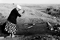 Kazakhstan. Aralsk. Marzhan Apai Serggziyeva washes her hands from a natural water spring. The old woman wears a headscarf on her head. As a young girl and a youg woman, she used to swimm in the Aral Sea in Aralsk. Due to the man-made environmental disaster by overuse of water resources and the environmental effects of industrial pollution in the former Soviet Union, the Aral sea started to dry up, then shrunk and is now two shallow lakes far from the old shore (100 km distant). Aralsk is located in the Kyzyl Orda Province. © 2008 Didier Ruef ... ..