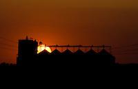 Summer sun sets behind grain storage and mill facility