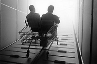 Switzerland. Canton Bern. Bienne. Expo 02. Migros area. Sideshow: Strangers in paradise. Two men side by side, a couple seated in a maxi shopping cart, on their way to the sky. © 2002 Didier Ruef