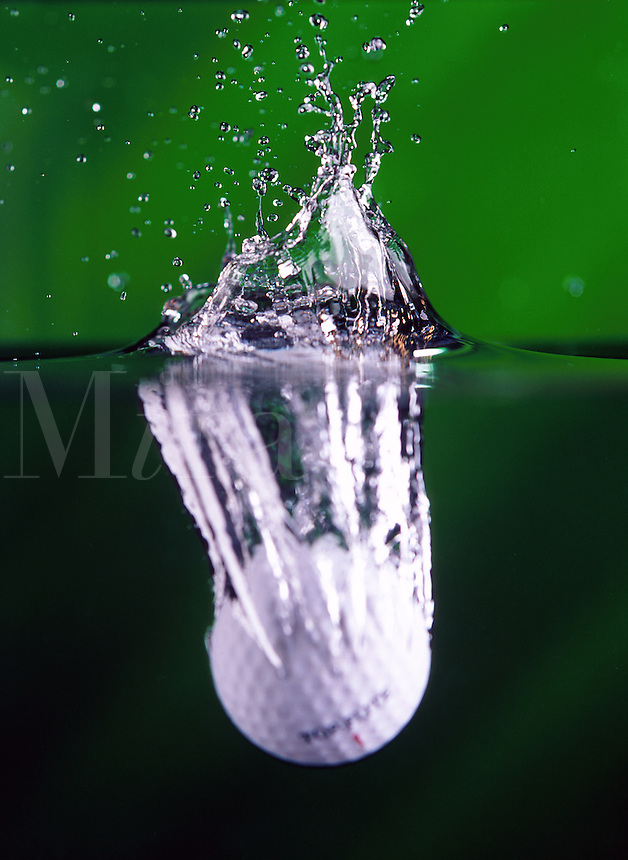 A golf ball splashes into water.