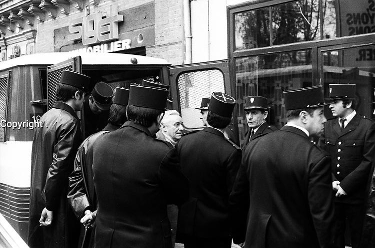 """""""Portai [Portay], Picard, Me Cathala, Me Bouscatel, Me Rastoul"""". Rue d'Aubuisson. 30 novembre 1976. Vue d'ensemble de Claude Birague sortant d'un fourgon de police, policiers autour. Cliché pris le jour d'une reconstitution judiciaire dans le cadre de l'affaire du meurtre de René Trouvé. Observation: Affaire René Trouvé-Birague : le 19 février 1976, le journaliste René Trouvé est assassiné d'une balle dans la tête, par deux inconnus, alors qu'il regagne son domicile au 33 rue Bayard"""