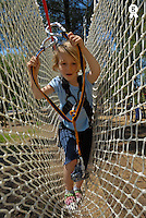Girl (5-7), holding rope, crossing netting in adventure playground (Licence this image exclusively with Getty: http://www.gettyimages.com/detail/200502957-001 )