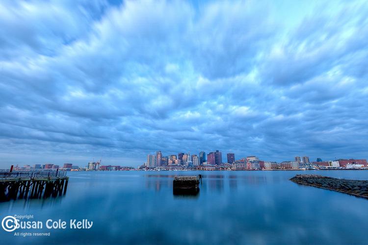 A dramatic, cloudy sunrise over Boston Harbor, Boston, Massachusetts, USA
