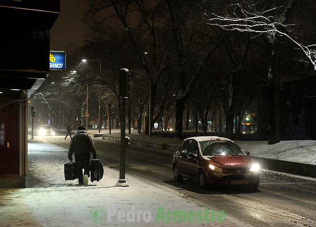 a man walks with two suitcases under the snow in Madrid during a cold tempral on January 10, 2010<br /> (c)Pedro Armestre
