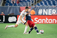 FOXBOROUGH, MA - MAY 22: Tommy McNamara #26 of New England Revolution passes the ball under pressure from Sean Davis #27 of New York Red Bulls during a game between New York Red Bulls and New England Revolution at Gillette Stadium on May 22, 2021 in Foxborough, Massachusetts.