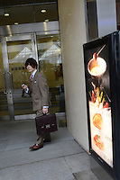 Young businessman with mobile phone comes out from the building in Shinjuku, Tokyo