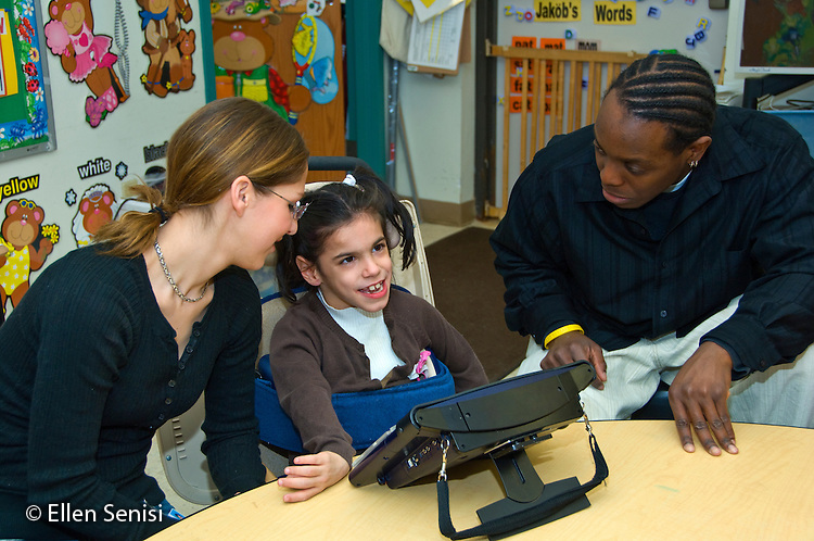 MR / Albany, NY.Langan School at Center for Disability Services .Ungraded private school which serves individuals with multiple disabilities.Two aides help a student use an alternative and augmentative communication device during speech and language development lesson. Girl: 7 cerebral palsy, nonvebal with expressisve and receptive language delays..MR: Wes2, Del16, Gil10.© Ellen B. Senisi
