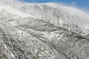 Mount Washington - Huntington Ravine in extreme weather conditions from Boott Spur Trail in the White Mountains, New Hampshire USA during the winter months. Strong winds cause snow to blow across the mountain tops.