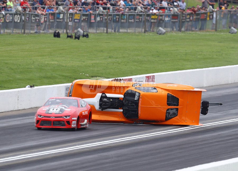 Jun 9, 2019; Topeka, KS, USA; NHRA pro mod driver Jeremy Ray (right) flips over as he races alongside Erica Enders during the Heartland Nationals at Heartland Motorsports Park. Ray would be transported to a local hospital for evaluation. Mandatory Credit: Mark J. Rebilas-USA TODAY Sports