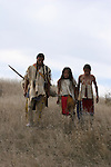 Three young Native American Indian boys walking through the dry grass on the Plains of South Dakota