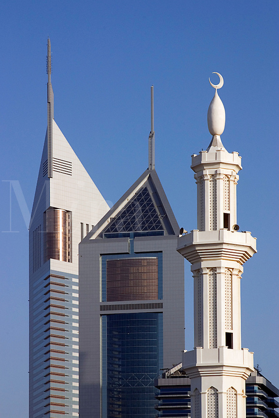 Dubai, United Arab Emirates. Emirates Towers with the minarets of a mosque in the foreground. Sheikh Zayed Road, the Abu Dhabi Road, .
