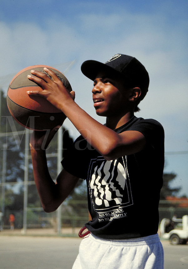 AFRICAN-AMERICAN TEEN SHOOTING HOOPS IN THE PARK. AFRICAN-AMERICAN TEEN. OAKLAND CALIFORNIA USA.