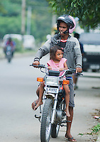 A man and his daughter ride a motorcycle in Dili, East Timor.