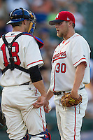 Wearing an Austin Senators throwback uniforms, Round Rock Express pitcher Evan Meek (30) talks on the mound with catcher Eli Whiteside (18) during the Pacific Coast League baseball game against the Oklahoma City RedHawks on July 9, 2013 at the Dell Diamond in Round Rock, Texas. Round Rock defeated Oklahoma City 11-8. (Andrew Woolley/Four Seam Images)
