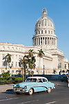 Havana, Cuba; a light blue classic 1951 Buick serves as a taxi during the morning commute along Paseo de Marti, with the Capitol building in the background