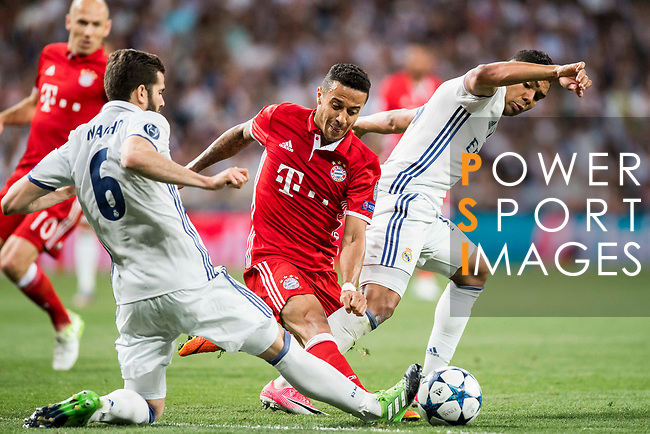 Thiago (c) of FC Bayern Munich battles for the ball with Carlos Henrique Casemiro (r) and Nacho Fernandez of Real Madrid during their 2016-17 UEFA Champions League Quarter-finals second leg match between Real Madrid and FC Bayern Munich at the Estadio Santiago Bernabeu on 18 April 2017 in Madrid, Spain. Photo by Diego Gonzalez Souto / Power Sport Images