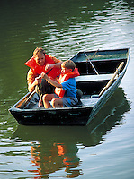 Twelve year old boy and adult male are proud of fish caught and held up to enjoy during an outing at a park lake in their rowboat wearing life jackets. Father and son.