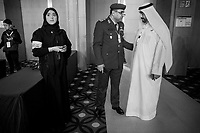 United Arab Emirates (UAE). Abu Dhabi. Unmanned Systems Exhibition (UMEX 2020). The woman wearing a black abaya and both men (R) are all Emirati citizens. The woman works for the conference committee and holds a smartphone in her hands. The military man talks to a man dressed with the traditional white thobe. A thawb (thobe, dishdasha, kandora) is an ankle-length garment, usually with long sleeves, similar to a robe, kaftan or tunic. It is commonly worn in the Arabian Peninsula. A sirwal or pants, izaar or lungi are typically worn underneath. The traditional headdress worn by Arab men is called ghutrah. The United Arab Emirates (UAE) is a country in Western Asia at the northeast end of the Arabian Peninsula. 22.02.2020  © 2020 Didier Ruef