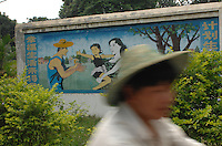 """Propoganda posters adorn the countryside that advise parents that tell them that having too many children will ruin socity. this one reads: """"a happy life is coming to you if you follow planning laws""""<br /> ©sinopix"""