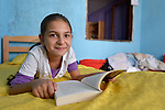 """THIS PHOTO IS AVAILABLE AS A PRINT OR FOR PERSONAL USE. CLICK ON """"ADD TO CART"""" TO SEE PRICING OPTIONS.   Sarah Ismili, an 11-year old Roma girl in Suto Orizari, the Macedonian municipality that is Europe's largest Roma settlement, reads her school homework in her family's home."""