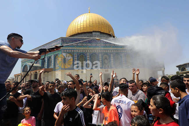 A Palestinian man sprays water at worshipers at Jerusalem's Al-Aqsa Mosque compound, Islam's third holiest site, on the third Friday of the holy month of Ramadan, on April 30, 2021. Photo by Jamal Awad