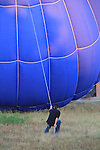 Man pulling on rope and a hot air balloon, Boulder, Colorado, USA.