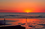 A runner puts in his daily miles while another pauses to watch the sun sinking into the Pacific.