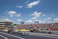 Jun. 2, 2013; Englishtown, NJ, USA: NHRA top fuel dragster driver Brittany Force (left) races alongside Spencer Massey during the Summer Nationals at Raceway Park. Mandatory Credit: Mark J. Rebilas-