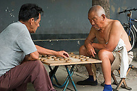 Two men playing Chinese chess on a sidewalk, Hutong district, Beijing, China.