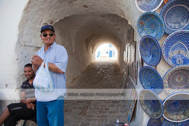 Ceramic plates and other handicrafts for sale line the entrance to a passageway in Sidi Bou Said, a charming town near the Tunisian capital.