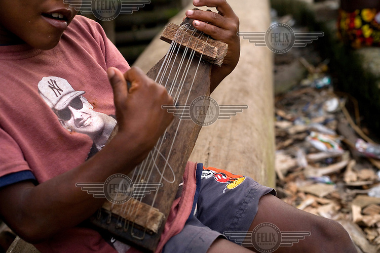 A child plays a homemade guitar as he sits on a bench on the island of Limones.