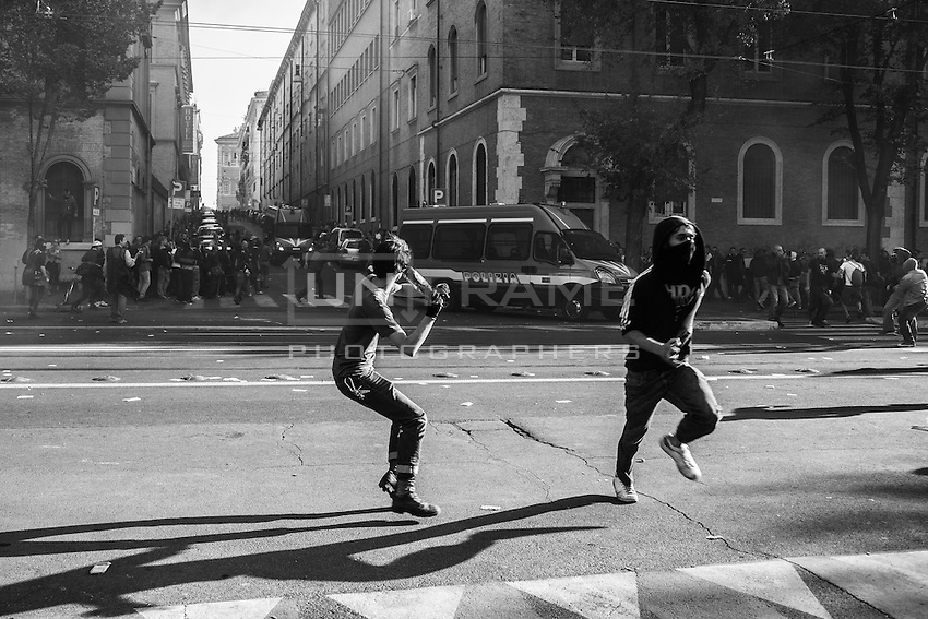 Rioters throw bottles against the police during the urban guerilla triggered by black blocs fringes. Rome, Italy. 15/10/2011