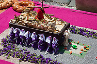 Antigua, Guatemala.  An alfombra (carpet) of flowers, pine needles, colored sawdust, and other traditional materials decorates the street in advance of the passage of a procession during Holy Week, La Semana Santa.  This alfombra contains a miniature model of an anda (float), borne by cucuruchos (men in purple tunics), similar to the real one that will soon pass over this alfombra, destroying it in the process.  Street sweepers will follow behind the anda, carrying away all the remains of the alfombra within minutes of the passage of the religious procession.