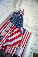 John Gandy (lower right), facilities maintenance supervisor, Arlington National Cemetery; assists Dan Frye (top left), facilities maintenance electrian, Arlington National Cemetery; in hanging American flags in the Memorial Amphitheater in preparation for Memorial Day at Arlington National Cemetery, Arlington, Virginia, May 21, 2018. 43 American flags are hung in the Memorial Amphitheater twice a year during observance of Memorial Day and Veterans Day (U.S. Army photo by Elizabeth Fraser / Arlington National Cemetery / released)