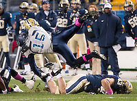 Pitt's kick defenders Titus Howard (18) and Mark Giubilato (43) punish Old Dominion ball carrier Aaron Evans (15). The Pitt Panthers defeated the Old Dominion Monarchs 35-24 at Heinz Field, Pittsburgh, Pennsylvania on October 19, 2013.