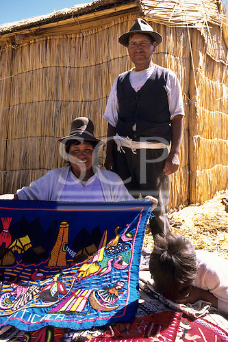 Lake Titicaca, Peru. Man and woman showing souvenir embroidered cloths on the floating island of Uros.