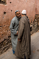 Marrakesh, Morocco.  Two Men Greeting Each Other in the Street.