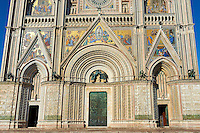 close of the doors and Gothic sculptures of  the14th century Tuscan Gothic style facade of the Cathedral of Orvieto, designed by Maitani, Umbria, Italy