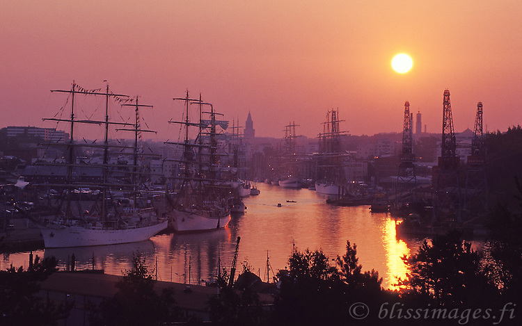 Tall ships berthed alongside the Aura River awaken at sunrise in Turku, Finland 2003.