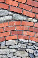Brick and rock wall with fuchia plant. Bandon Oregon