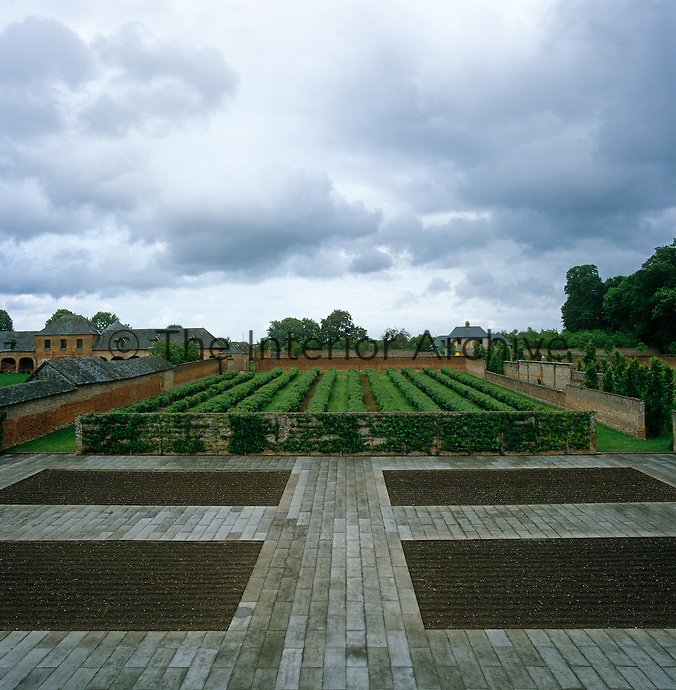 Formal flowerbeds surrounded by paved walkways give way to neat rows of vines within the walled kitchen garden