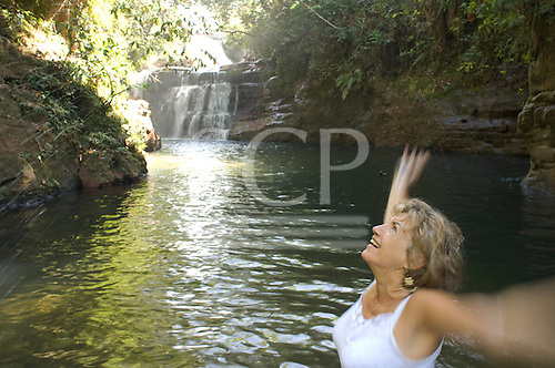 Brazil. Canarana to Barra do Garcas. Sue Cunningham at the Cataratas Cristal waterfall.