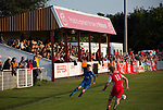 Spectators in the stand watching the first-half action at Yockings Park as Whitchurch Alport (in red) hosted Cammell Laird 1907 in the 2017-18 North West Counties Division One play-off final. Alport were formed in 1946 and were named after Alport Farm, Whitchurch, which had been the home of a local footballer Coley Maddocks who had been killed in action in the war. The home team won the match 2-1 watched by a crowd of 733, a club record attendance.