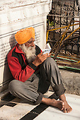 Amritsar, Punjab, India.  The Golden Temple - Harmandir Sahib - with an old grey bearded Sikh man in an orange turban sitting on the floor reading from a holy book, barefoot.